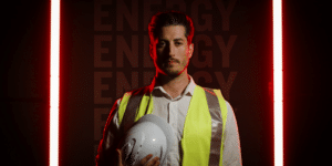 Worker stands in front of red backdrop for video advertisement