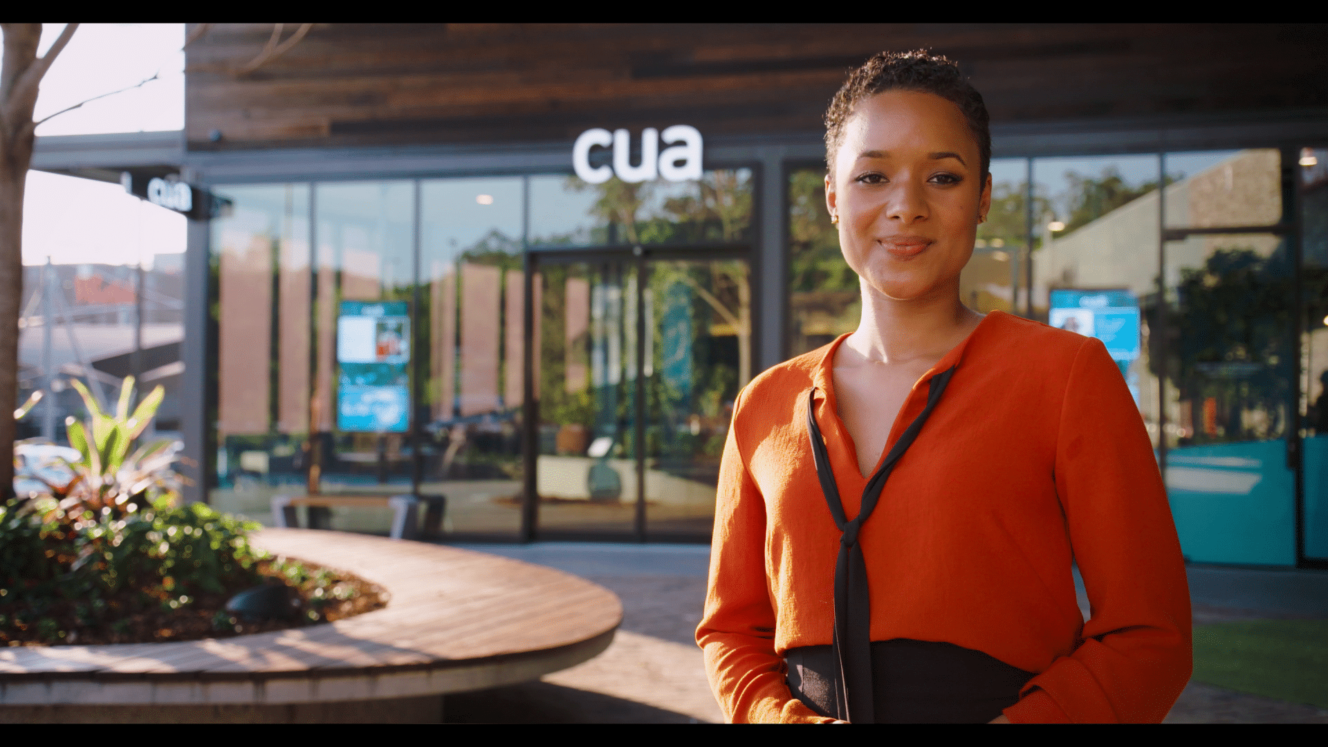 Corporate video presenter stands in front of a CUA branch on a sunny day.