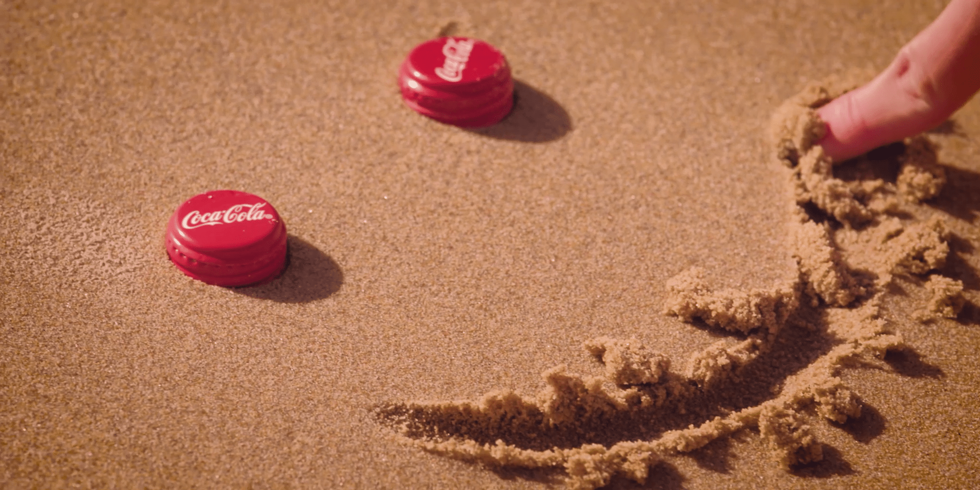 An image from a coke commercial video: Two bottle caps in the sand with a smiling mouth drawn beneath.