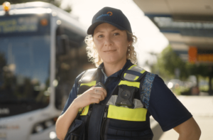 Female safety officer poses in front of bus
